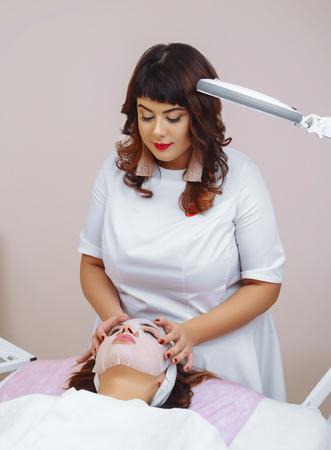 Photo pour Beautiful woman with facial mask at beauty salon - image libre de droit