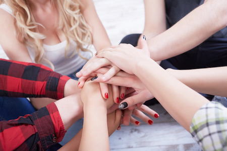 group of students in a bright room on the floor sit in a circle holding hands