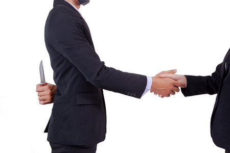Photo for Stab back,two business men making a deal but hiding knives - Royalty Free Image