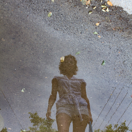 a reflection of a young girl in a puddle after rain.
