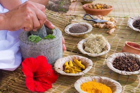 Foto de Asian hands preparing ayurvedic medicine with granite mortar and pestle. - Imagen libre de derechos