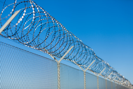 Photo pour Coiled razor wire with its sharp steel barbs on top of a wire mesh perimeter fence ensuring safety and security, preventing access or the escape of prisoners, blue sky background - image libre de droit