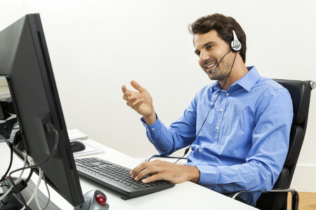 Foto de Attractive unshaven young man wearing a headset offering online chat and support on a client services of help desk as he types in information on his computer - Imagen libre de derechos