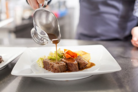 Foto de Chef plating up food in a restaurant pouring a gravy or sauce over the meat before serving it to the customer, close up view of his hand and the gravy boat - Imagen libre de derechos