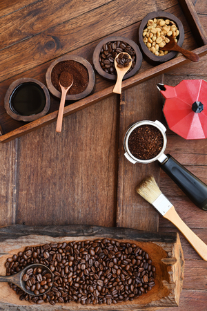 Foto de Freshly ground coffee beans in a metal filter and coffee beans with red kettle on the side. - Imagen libre de derechos