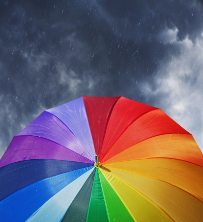 Rainbow umbrella on stormy sky background in heavy rain