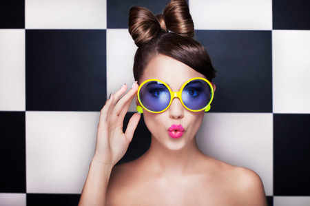 Photo pour Attractive surprised young woman wearing sunglasses on checkered background, beauty and fashion concept  - image libre de droit