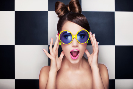 Photo for Attractive surprised young woman wearing sunglasses on checkered background, beauty and fashion concept  - Royalty Free Image