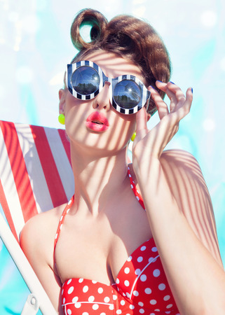 Photo pour Colorful summer portrait of young attractive woman wearing bikini and sunglasses sitting by the swimming pool - image libre de droit