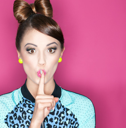 Foto de Young attractive fashionable woman with finger on lips, secret concept - Imagen libre de derechos