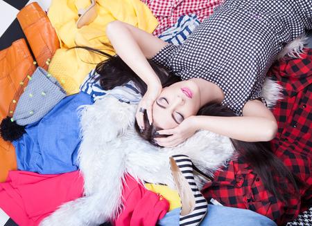 Foto de Nothing to wear concept, woman lying on a pile of clothes - Imagen libre de derechos