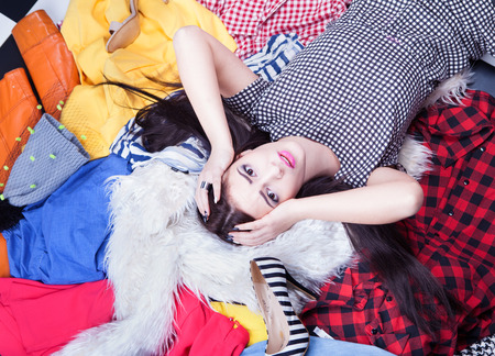 Photo for Stressed young woman lying down on a pile of clothes - Royalty Free Image