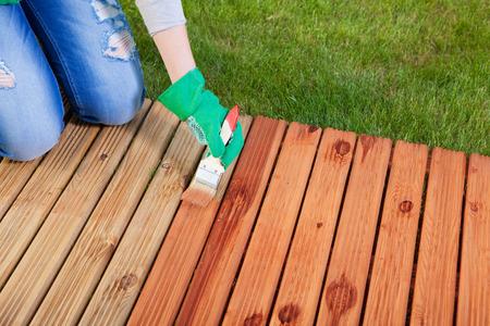 Photo pour Applying protective varnish on a patio wooden floor, maintenance concept - image libre de droit