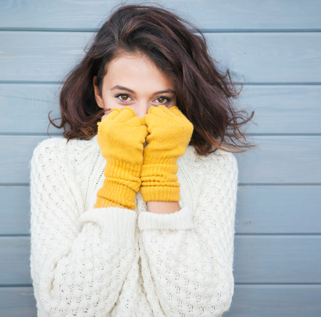 Photo pour Beautiful natural young smiling brunette woman wearing knitted sweater and gloves. Fall and winter fashion concept. - image libre de droit