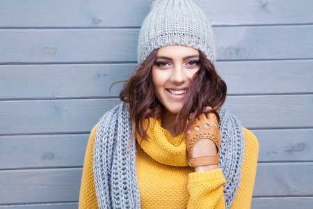 Photo pour Beautiful natural young smiling brunette woman wearing knitted sweater, leather gloves, scarf and hat. Covered with snow flakes. Fall and winter fashion concept. - image libre de droit