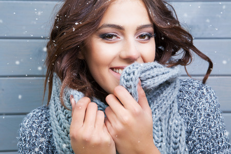Photo for Beautiful natural looking young smiling brunette woman, wearing knitted scarf, covered with snow flakes. Snowing winter beauty concept. - Royalty Free Image