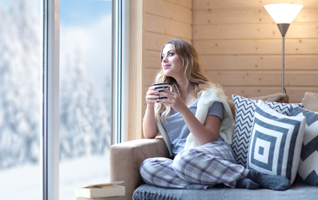Photo for Young beautiful blonde woman with cup of coffee sitting home in living room by the window. Winter snow landscape view. Lazy day off concept - Royalty Free Image