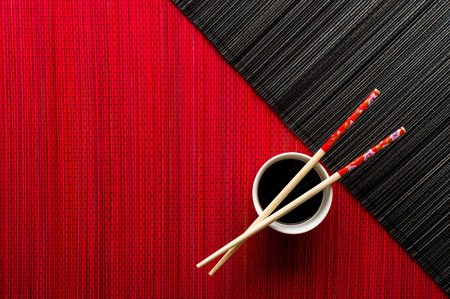 Photo for Chopsticks and bowl with soy sauce on bamboo mat - Royalty Free Image