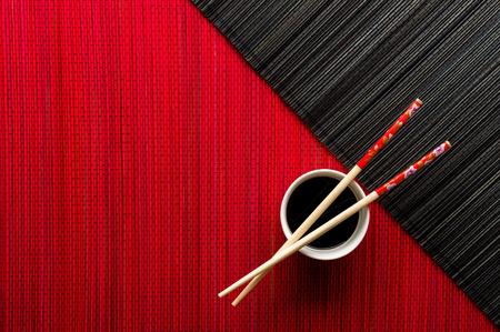 Foto de Chopsticks and bowl with soy sauce on bamboo mat - Imagen libre de derechos