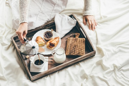 Photo for Woman having breakfast in bed. Window light - Royalty Free Image