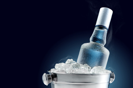 Foto de Bottle of cold vodka in bucket of ice on dark background - Imagen libre de derechos