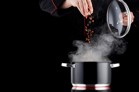 Foto de Modern chef in professional uniform adding spice to steaming pot - Imagen libre de derechos