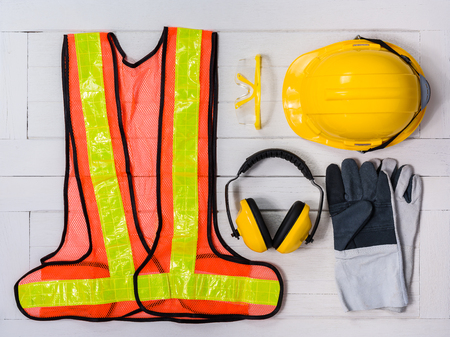 Foto de Standard construction safety equipment on white wooden background. top view, safety first concepts - Imagen libre de derechos