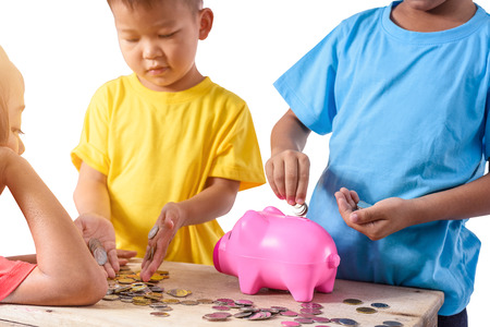Photo for Group of asian children are helping putting coins into piggy bank on white background. Education Savings concepts - Royalty Free Image