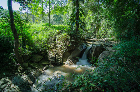 Photo pour Small waterfall on mountain stream in summer meadow of Thailand. Cold misty and rainy weather at the end of summer. - image libre de droit