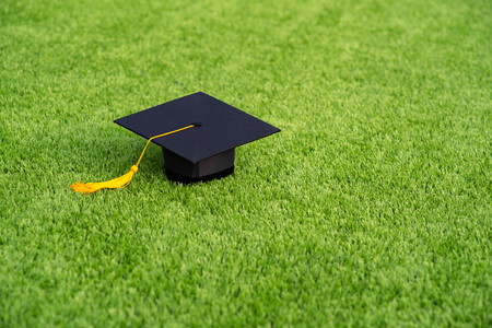 Photo pour Graduation Black hat and yellow tassel pace on Green field - image libre de droit