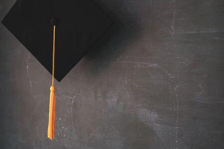Foto de Black graduates hat hung on the blackboard - Imagen libre de derechos