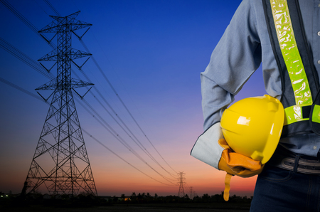 Foto de Engineer holding a yellow helmet for the safety of workers on the background. Silhouette transmission towers on the background of the evening sun. - Imagen libre de derechos