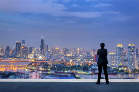 Photo pour Vision concept. Successful businessman standing with hands crossed on chest, On top of building and looking through Cityscape Skyline Night Light. - image libre de droit