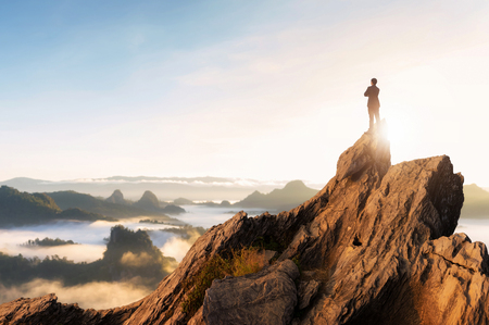 Photo pour Concept vision, Young businessman wearing comfortable casual suit jacket standing chest hug on top of peak mountain and looking forwards, success, competition and leader concept. - image libre de droit