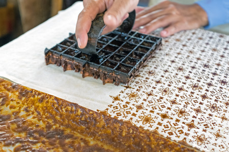 Foto de Printing on the fabric to make batik. Batik is part of the indonesian culture. - Imagen libre de derechos
