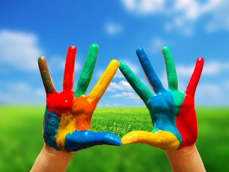 Foto de Painted colorful hands showing way to clear happy life, conceptual. Sunny perfect landscape - Imagen libre de derechos