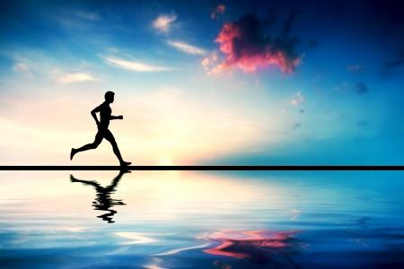 Foto de Silhouette of man running at sunset. Water reflection - Imagen libre de derechos
