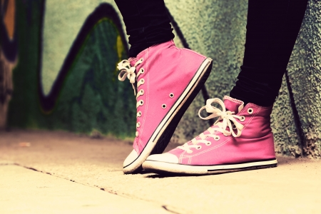 Photo pour Close up of pink sneakers worn by a teenager. Grunge graffiti wall, retro vintage style - image libre de droit