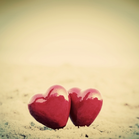 Two red hearts on the beach symbolizing love, Valentine