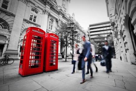 Foto de Business life concept in London, the UK  Red phone booth, people in suits walking - Imagen libre de derechos