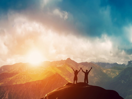 Photo pour A happy couple standing together on the peak of a mountain with hands raised admiring breathtaking view at sunset - image libre de droit