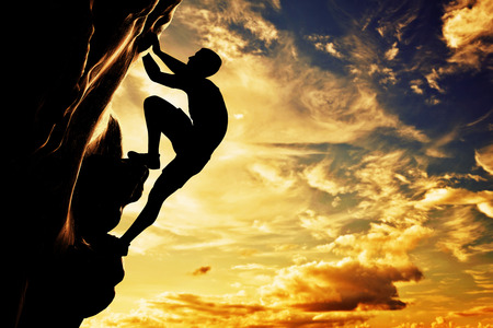 A silhouette of man free climbing on rock, mountain at sunset  Adrenaline, bravery, leader