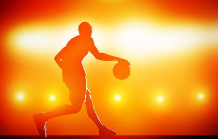 Basketball player silhouette dribbling with ball on red background with action lights