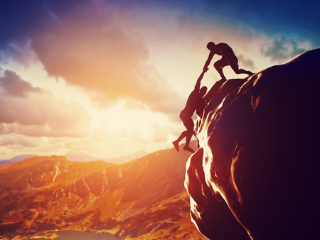 Photo pour Hikers climbing on rock, mountain at sunset, one of them giving hand and helping to climb  Help, support, assistance in a dangerous situation - image libre de droit