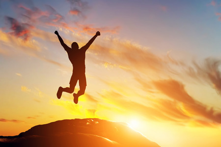 Foto de Happy man jumping for joy on the peak of the mountain, cliff at sunset. Success, winner, happiness - Imagen libre de derechos