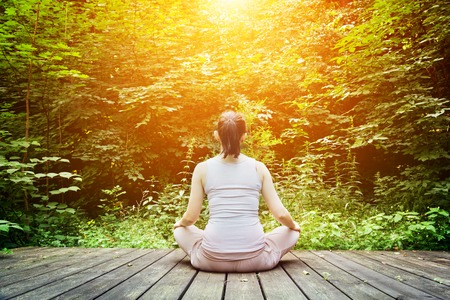 Photo for Young woman meditating in a forest sitting on a wooden floor. Zen, meditation, relax, spiritual health, healthy breathing - Royalty Free Image