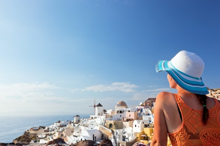 Photo for Happy woman in sun hat enjoying her holidays on Santorini island, Greece. View on Caldera and Aegean sea from Oia. Travel, tourist concepts - Royalty Free Image