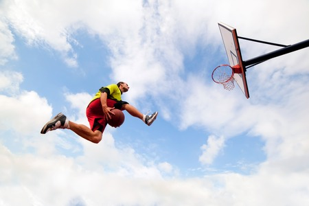 Photo pour Young man jumping and making a fantastic slam dunk playing streetball, basketball. Urban authentic. - image libre de droit