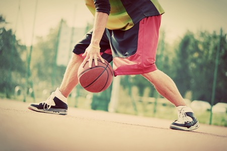 Photo pour Young man on basketball court dribbling with ball. Streetball, training, activity. Real and authentic, vintage mood. - image libre de droit