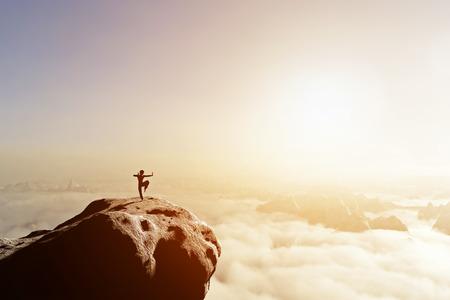 Foto de Asian man, fighter practices martial arts in high mountains above clouds at sunset. Kung fu and karate pose. Also concepts of discipline, concentration, meditaion etc. Unique - Imagen libre de derechos